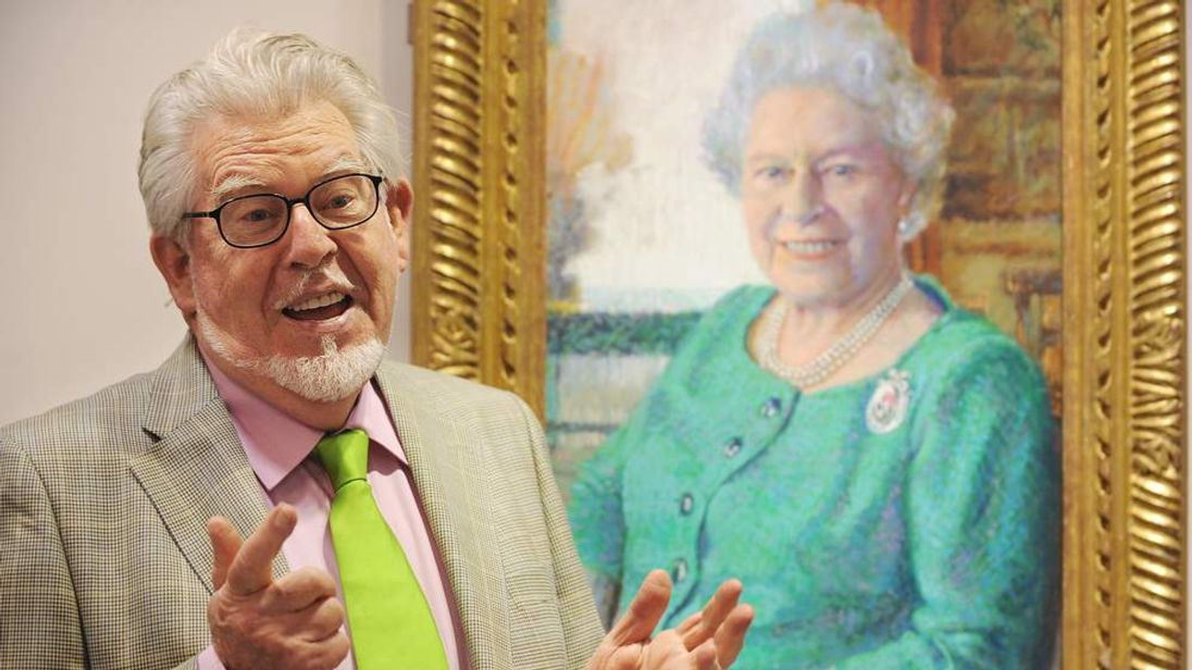 Rolf Harris poses with portrait of the Queen.