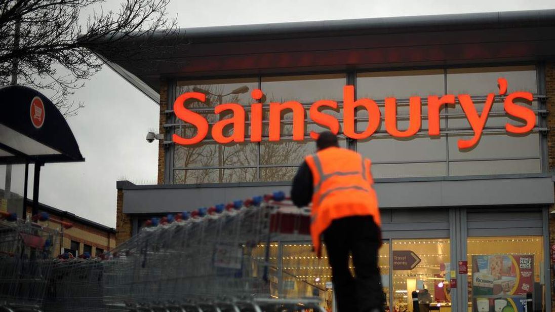 An employee moves shopping trolleys in front of a Sainsbury's store in London