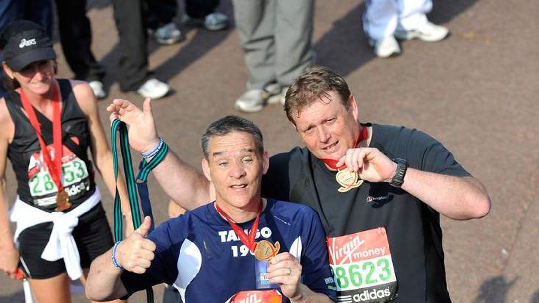 Pc David Rathband (L) completes the 2011 Virgin London Marathon
