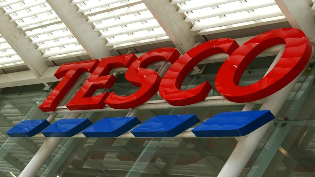 A Tesco sign hangs in front of the supermarket August 6, 2002