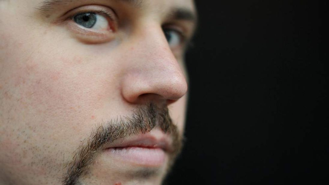 A man shows off his 'Movember' moustache