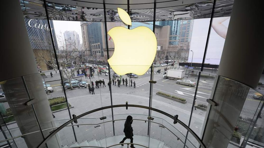 A customer walks under an Apple logo