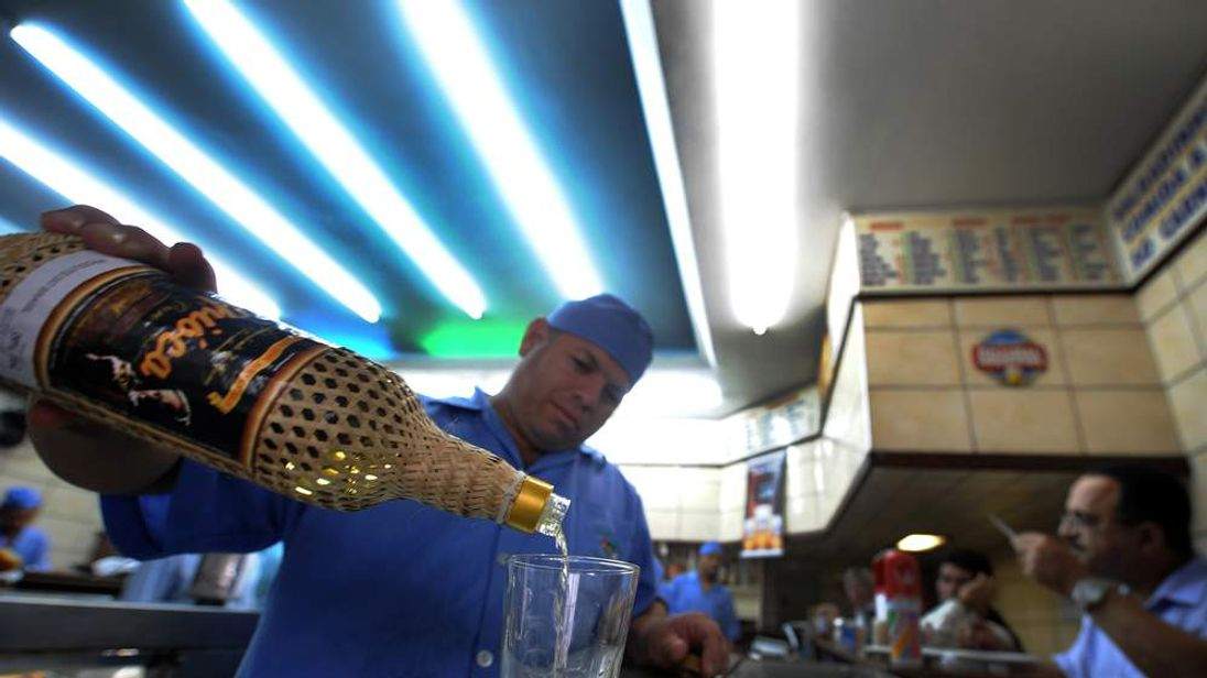 A waiter pours a measure of cachaca, Brazil's most popular spirit