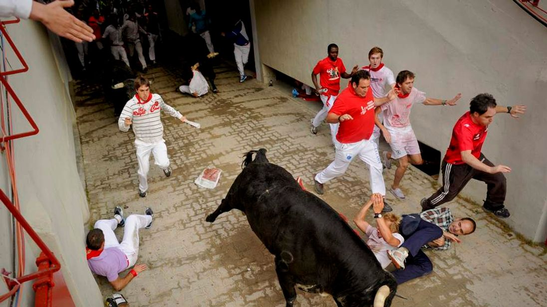 Runners take evasive action as fighting bull charges through streets of Pamplona