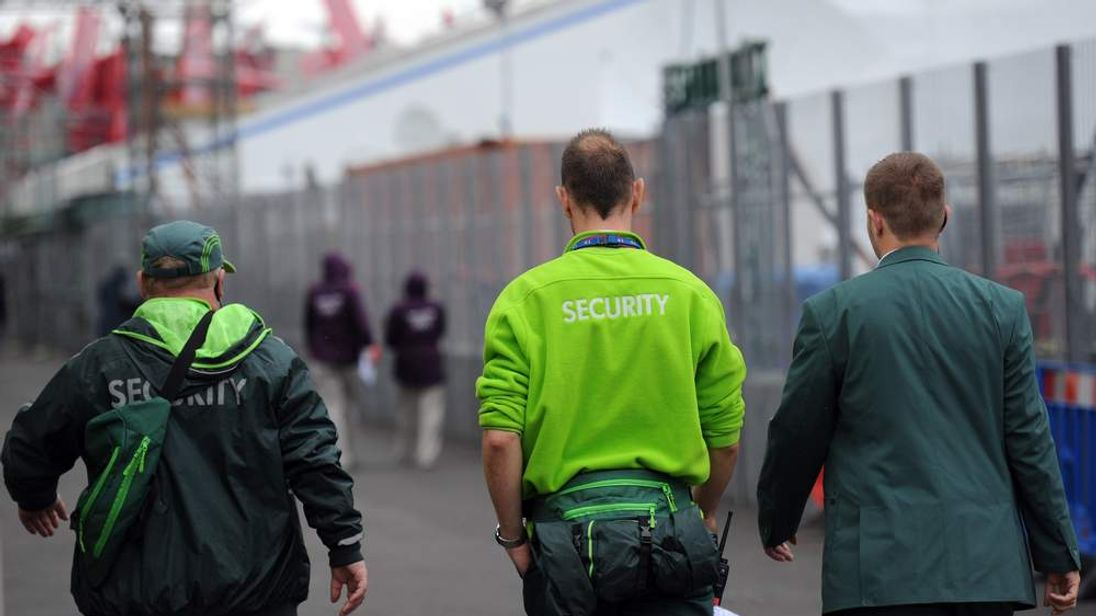 Security guards from the private firm G4S walk through the London 2012 Olympic Park