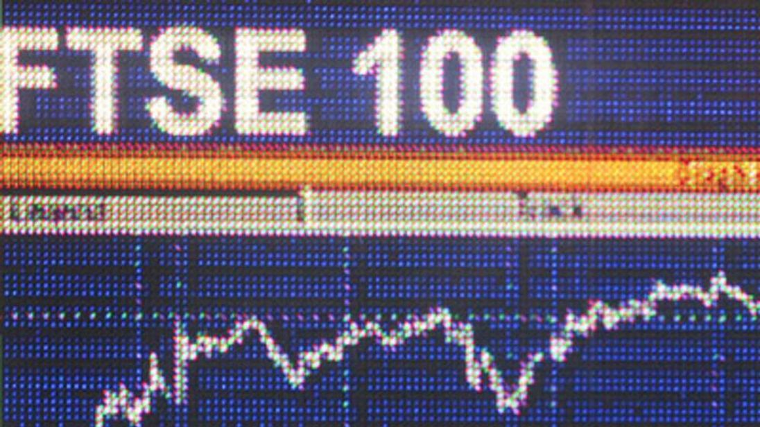 A screen shows a graph of the FTSE 100 share index