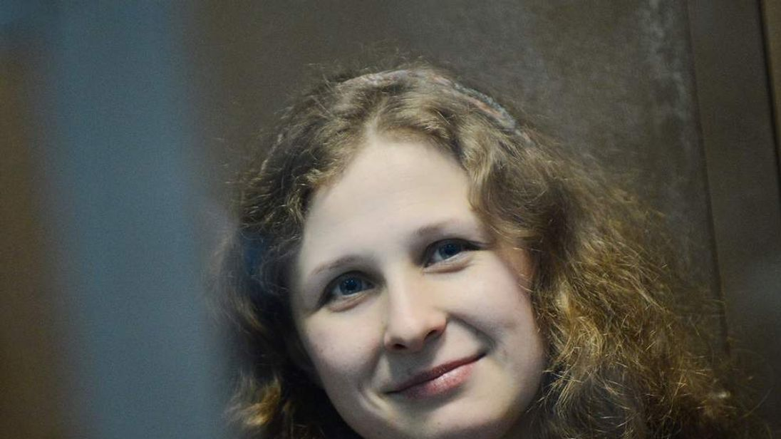 Pussy Riot band member Maria Alyokhina smiles while sitting in a glass-walled cage in a court in Moscow