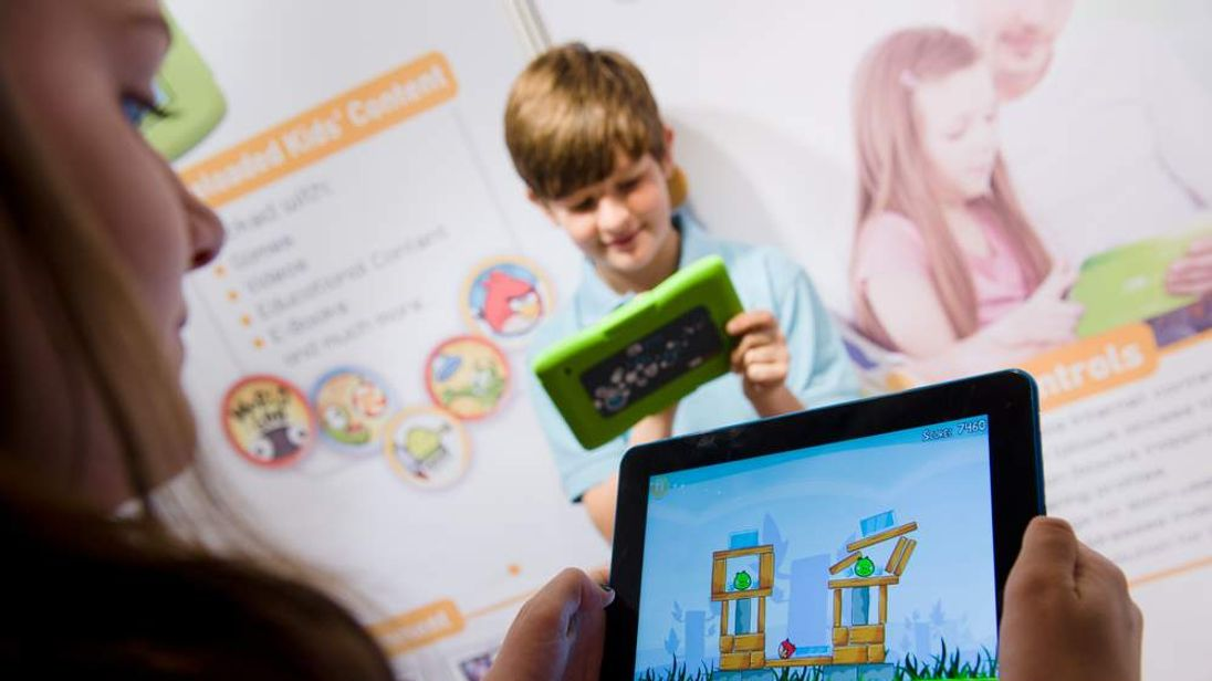 """Children play on the """"Kurio"""" Android-based family tablet."""