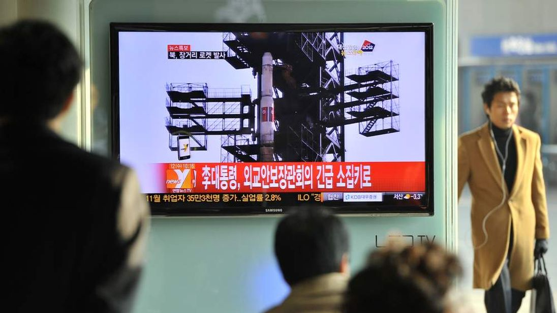 People in Seoul watch news of North Korea's rocket launch.