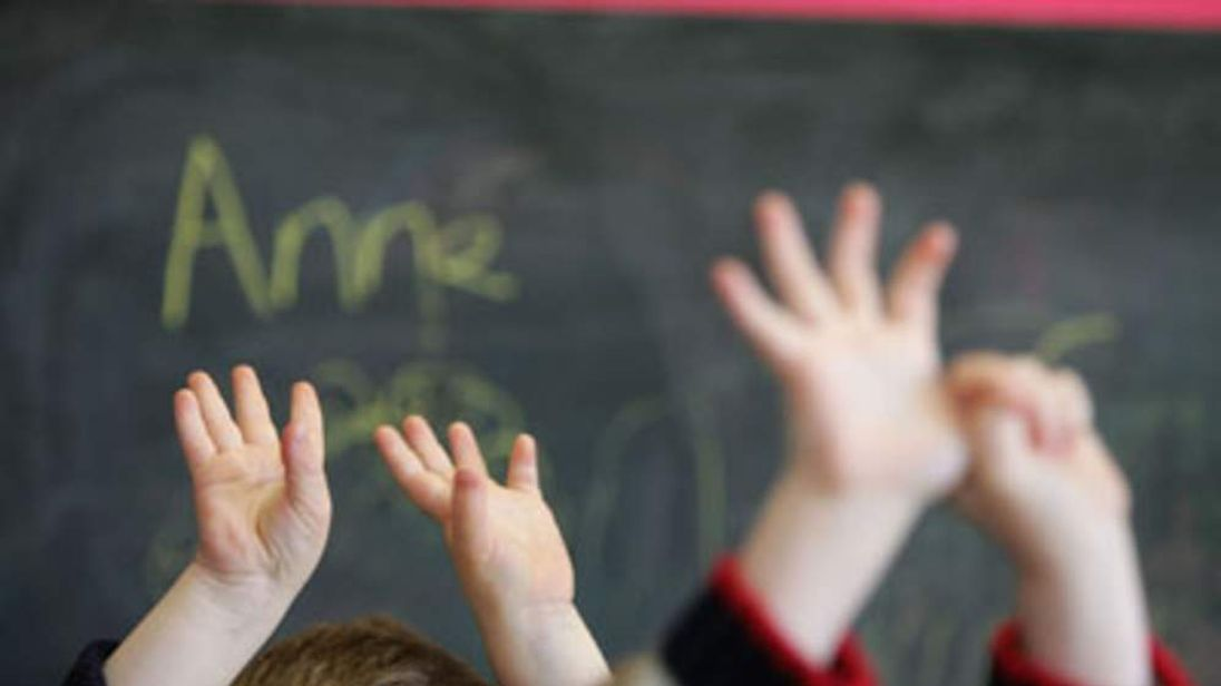 Children wave their hands at a private nursery school January 28, 2005 in Glasgow, Scotland.