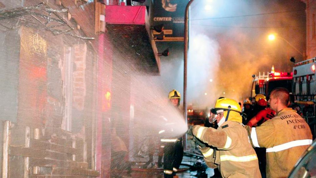 Firefighters try to put out a fire at a nightclub in Santa Maria
