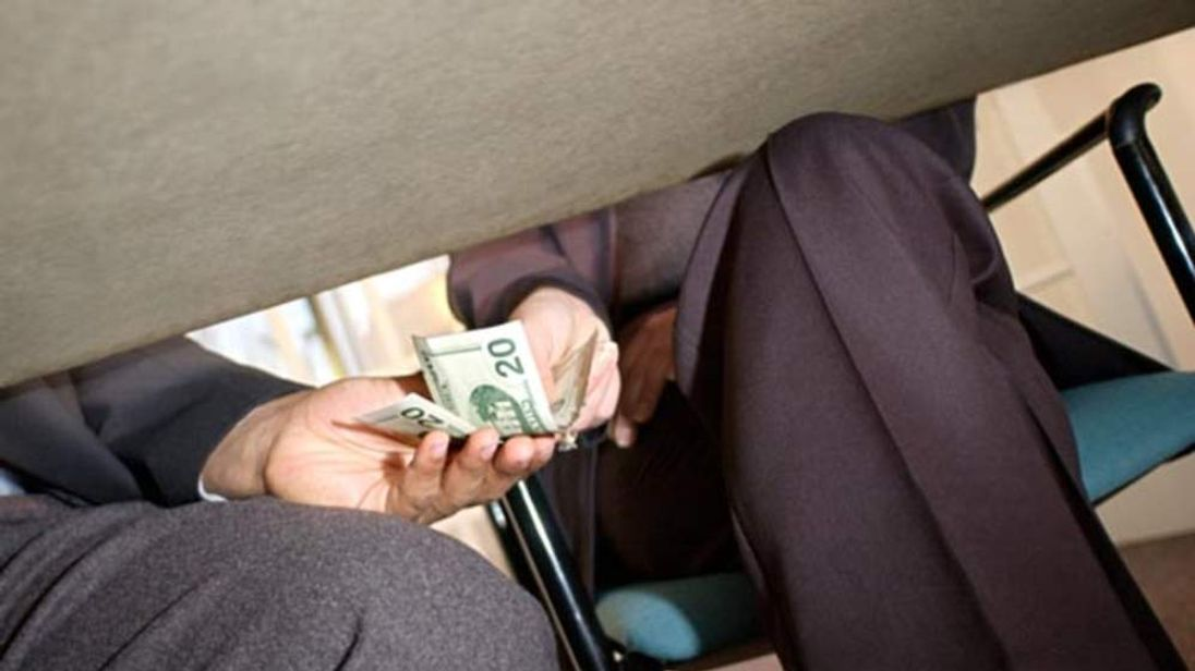 Businesspeople passing money under table