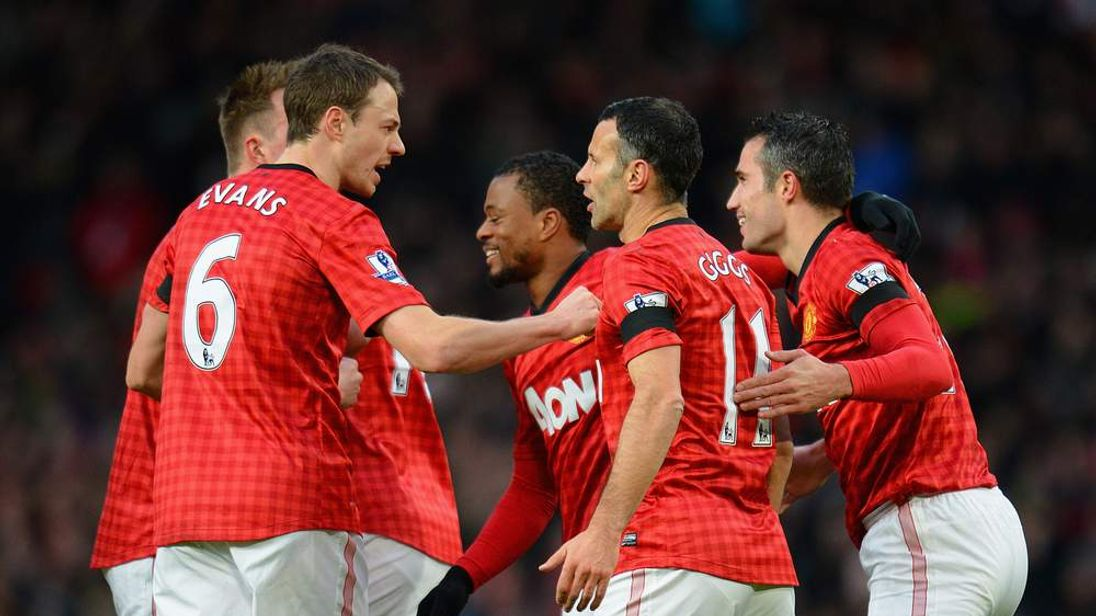 Manchester United players celebrate scoring their opening Premier League goal against Everton