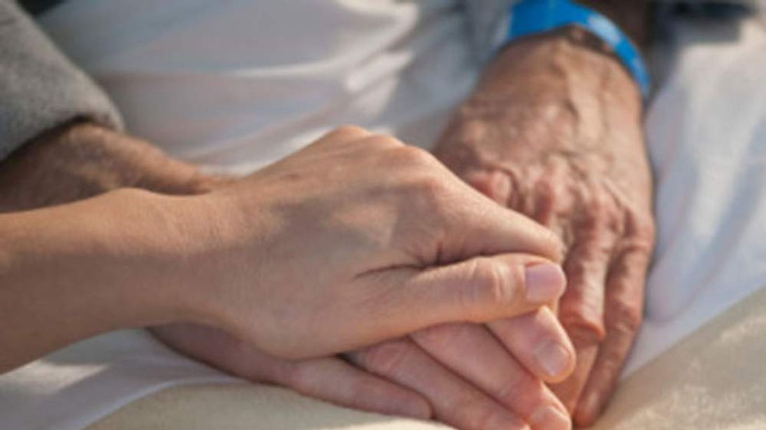 Nurse holding elderly mans hand