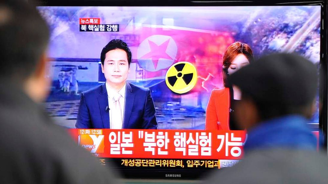 South Korean passengers watch TV news reporting North Korea's apparent nuclear test