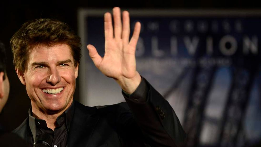 Cruise waves to fans at the premiere of Oblivion in Buenos Aires