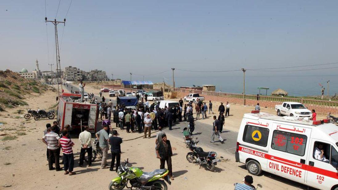 Palestinians gather around the scene following an Israeli raid on Gaza City