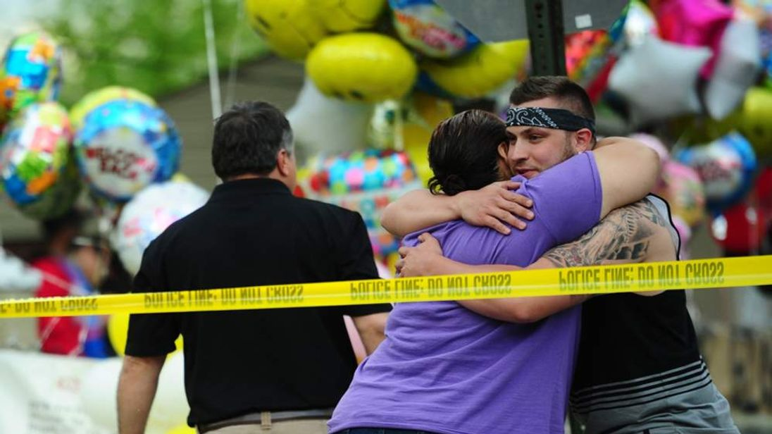 People embrace outside the home of Gina DeJesus, who was held captive for a decade