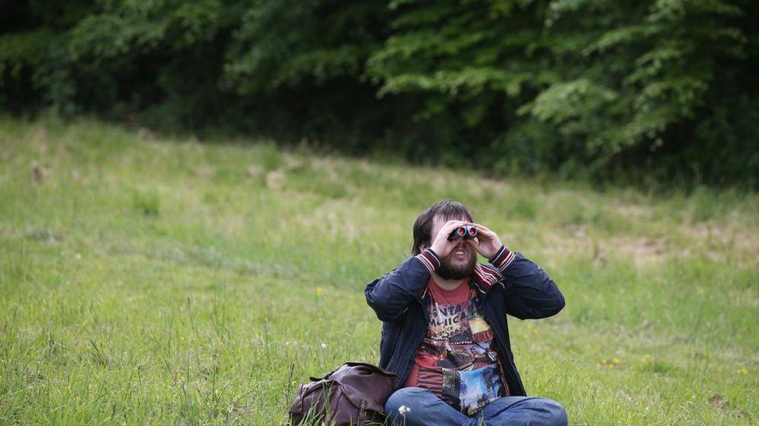 A man watches through binoculars