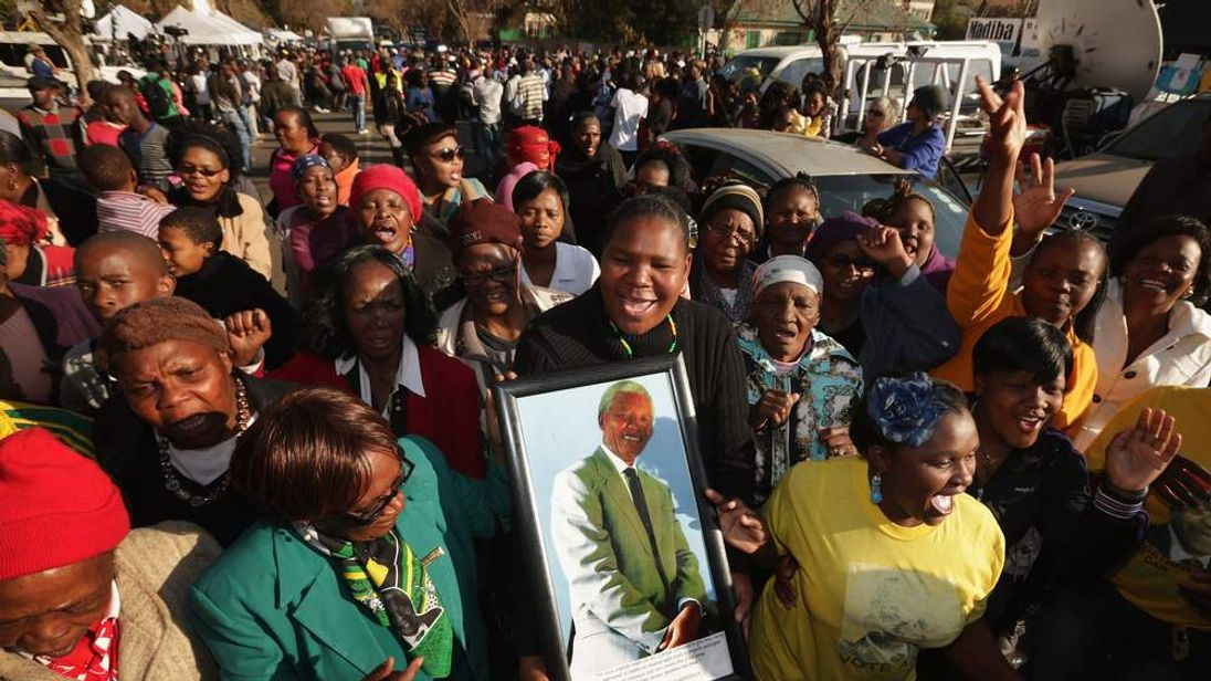 Well-wishers and supporters of former South African President Nelson Mandela march and sing outside the Mediclinic Heart Hospital