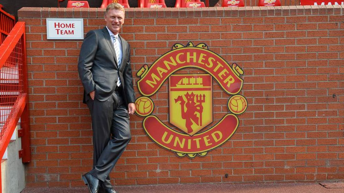 Manchester United's new manager David Moyes poses for photographers beside the club crest at Old Trafford.