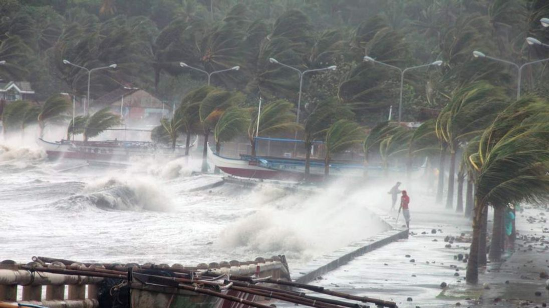 Residents (R) stand along a sea wall as high waves pounded them amidst strong winds as Typhoon Haiyan hit the city of Legaspi, Albay province, south of Manila