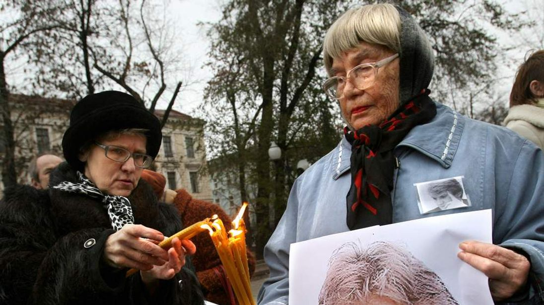 Women holding a poster of deceased forme