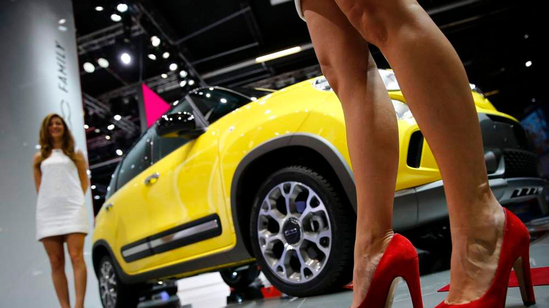 Models pose beside Fiat 500L Trekking car at Frankfurt motor show