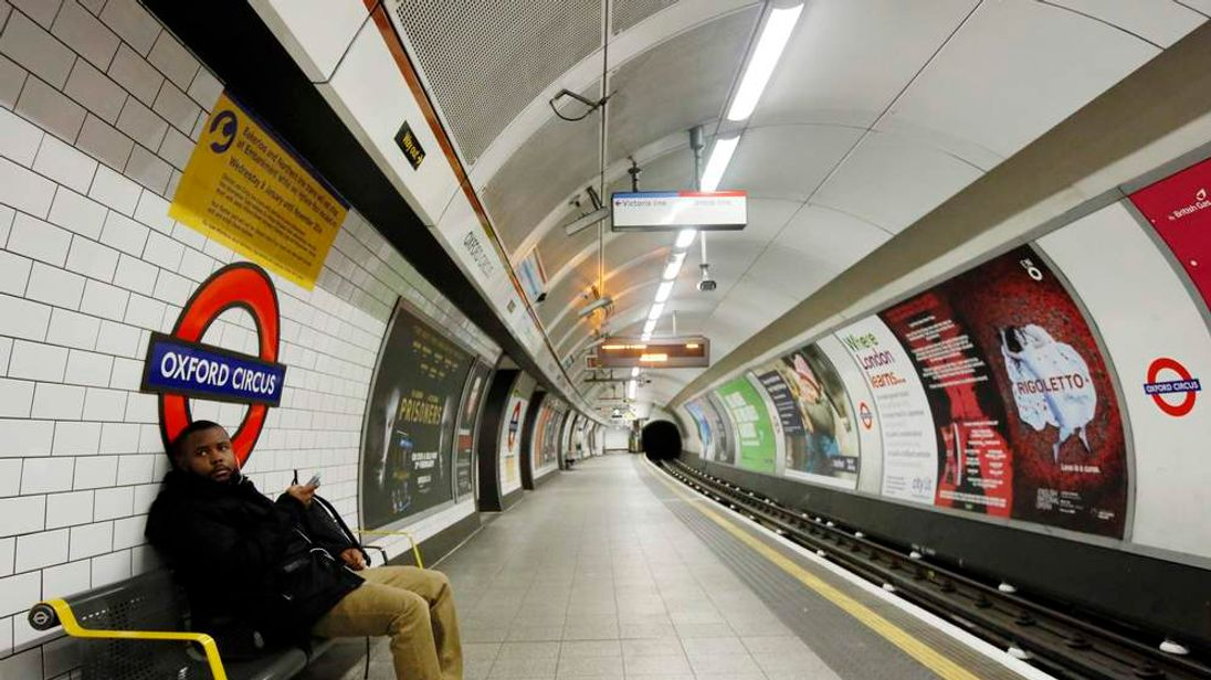 A passenger waits for a tube train that did not arrive on an empty platform during rush hour at Oxford Circus underground station in London