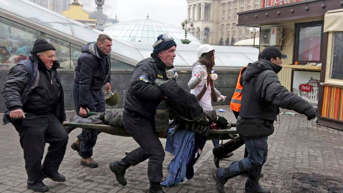 A wounded protester is rushed to a vehicle following violence in Independence Square in Kiev
