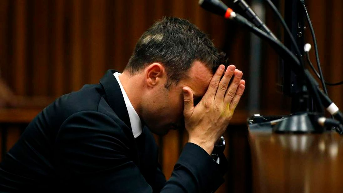Olympic and Paralympic track star Oscar Pistorius reacts in the dock ahead of his trial for the murder of his girlfriend Reeva Steenkamp, in Pretoria