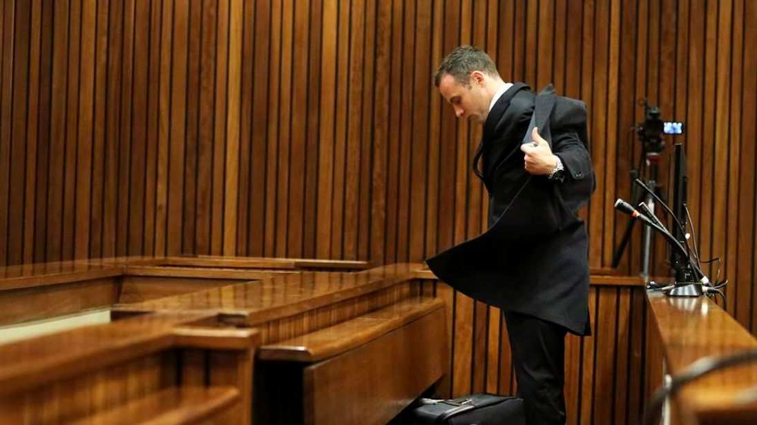Olympic and Paralympic track star Oscar Pistorius takes off his jacket after he entered the dock ahead of his trial for the murder of his girlfriend Reeva Steenkamp, at the North Gauteng High Court in Pretoria