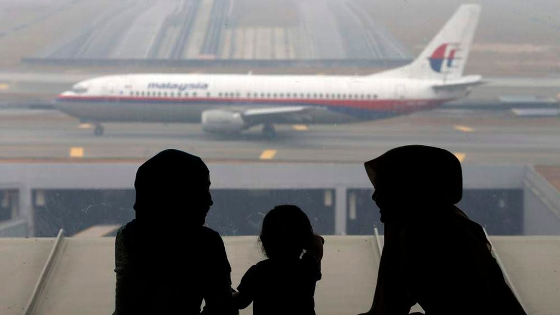 Women and a girl look at a Malaysia Airlines plane on the tarmac of Kuala Lumpur International Airport