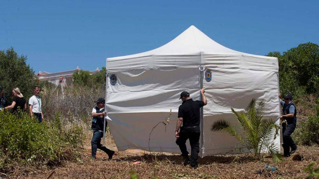 Scotland Yard detectives move a tent on an area during the search for missing British girl Madeleine McCann in Praia da Luz