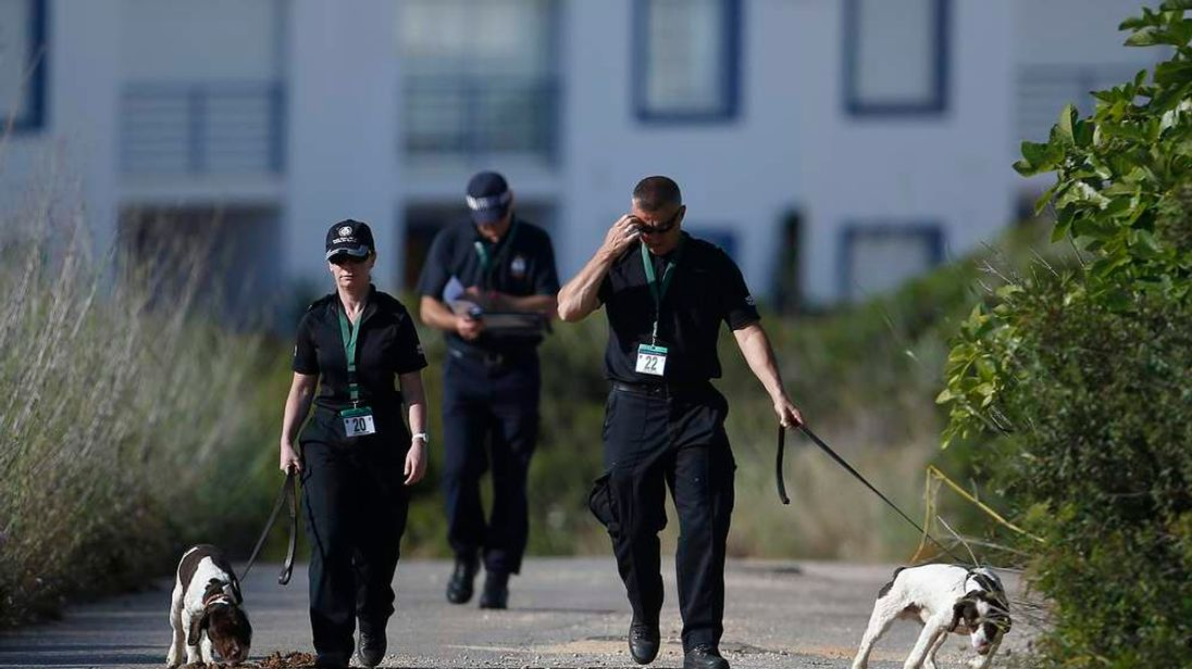 Scotland Yard detectives work with sniffer dogs on an area during the search for missing British girl Madeleine McCann in Praia da Luz