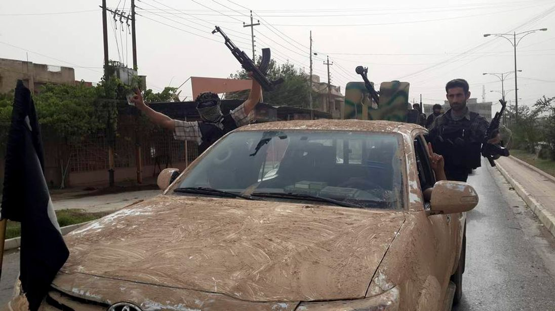 Fighters of the Islamic State of Iraq and the Levant (ISIL) celebrate on vehicles taken from Iraqi security forces, at a street in city of Mosul.