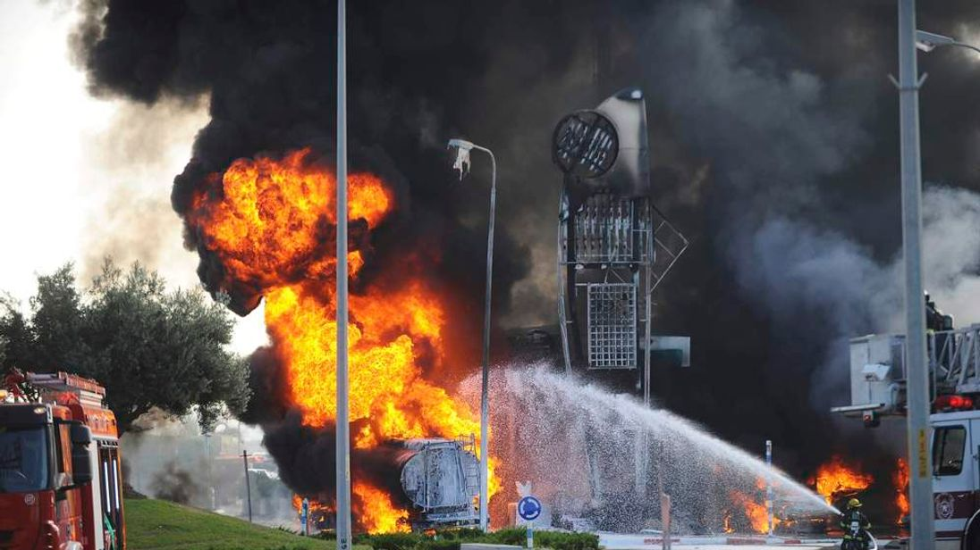 Israeli fire-fighters extinguish a fire that broke out after a rocket hit a petrol station in the southern Israeli city of Ashdod