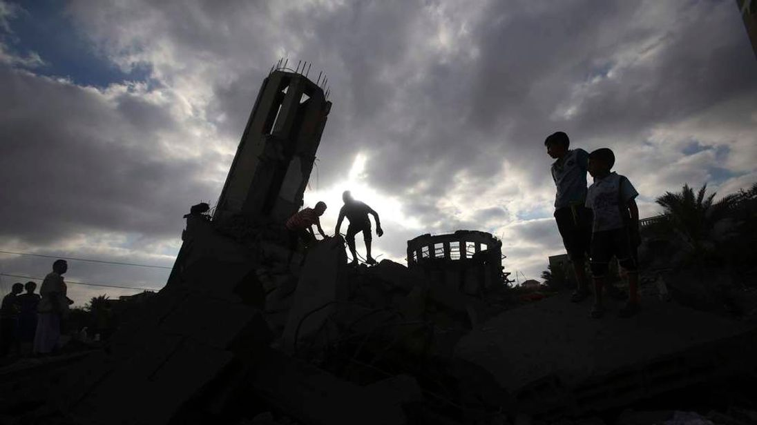 Palestinians stand atop the remains of a mosque, which witnesses said was destroyed in an Israeli air strike before a 72-hour truce, in Khan Younis