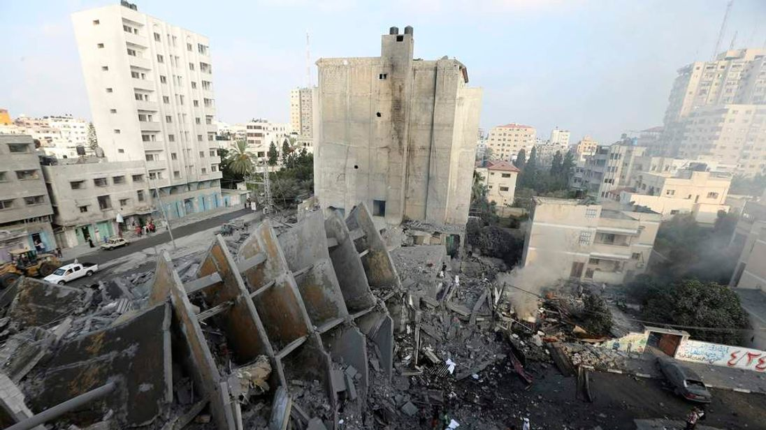 Palestinians gather around the remains of a tower building housing offices which witnesses said was destroyed by an Israeli air strike in Gaza City