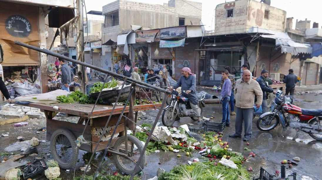 People inspect a site after hit by what activists said were air strikes by forces loyal to Syria's President Bashar al-Assad in Raqqa, eastern Syria, which is controlled by the Islamic State