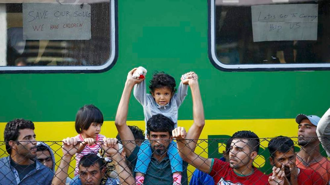 Migrants stand alongside train at Bicske railway station in Bicske
