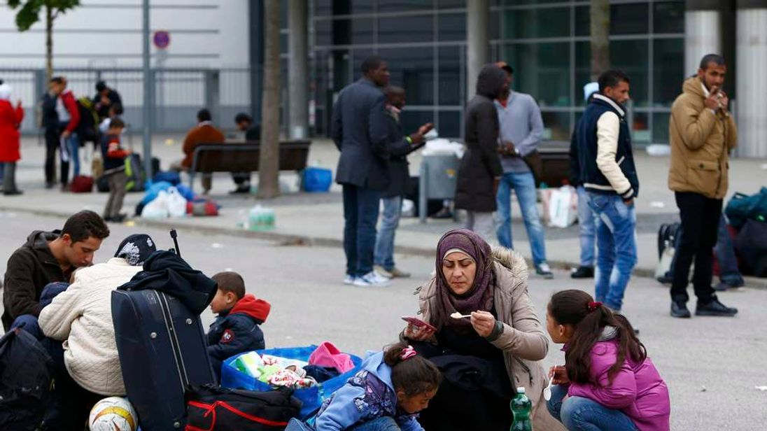 Migrants eat outside a makeshift refugee camp at the fair ground of Munich