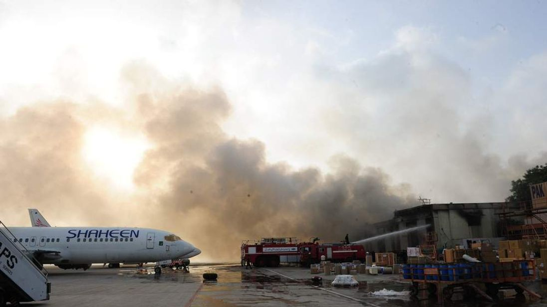 Pakistani firefighters extinguish fires after militants attack Jinnah International Airport in Karachi