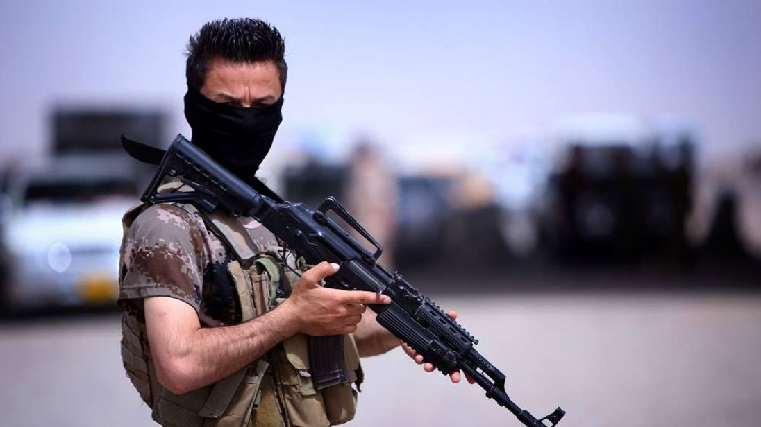 A masked Pershmerga fighter from Iraq's autonomous Kurdish region guards a temporary camp set up to shelter Iraqis fleeing violence in the northern Nineveh province,