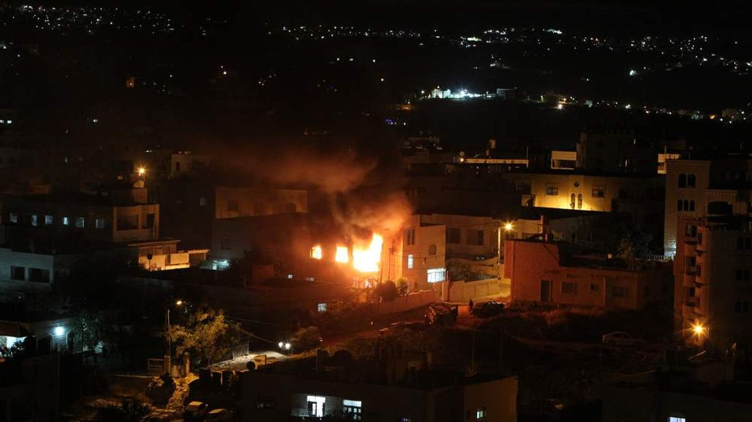 Flames and smoke billow from the blown-up house of Amer Abu Eisheh, one of two Palestinians suspected in the killing of three kidnapped Israelis