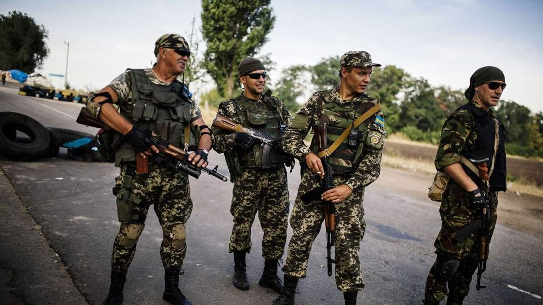Ukrainian soldiers stand guard at a checkpoint on a road near the city of Dnepropetrovsk.