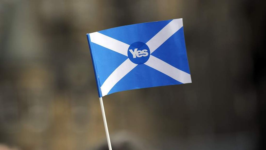 "A pro-independence supporter holds a ""Yes"" flag"
