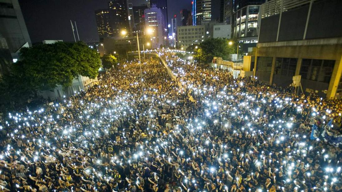Protesters hold up phones