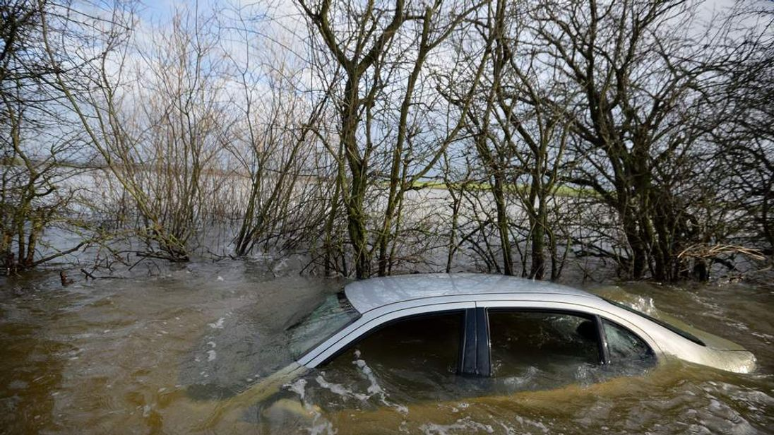 A car is seen submerged on the side of a flooded road leading into the cut-off village of Muchelney in Somerset