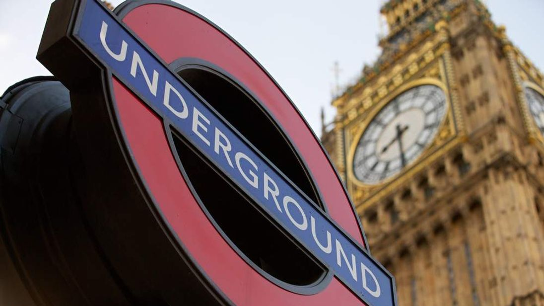 A London Underground Station sign is pictured against the backdrop of the Houses of Parliament in London